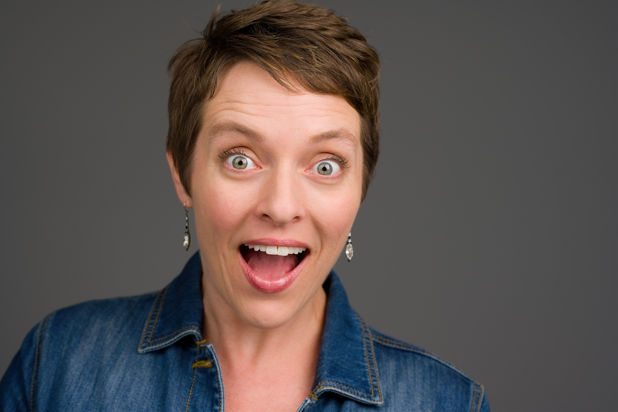 Woman expressing a happy surprise headshot.