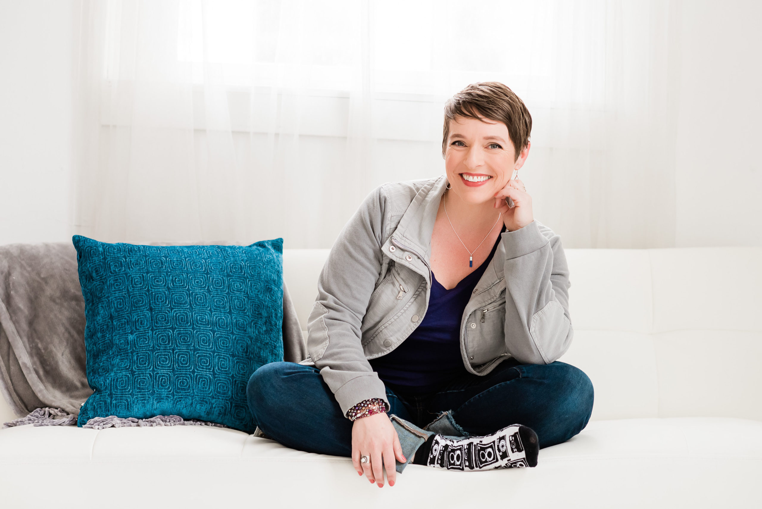 Smiling woman sitting cross legged on a white couch with blue pillow.