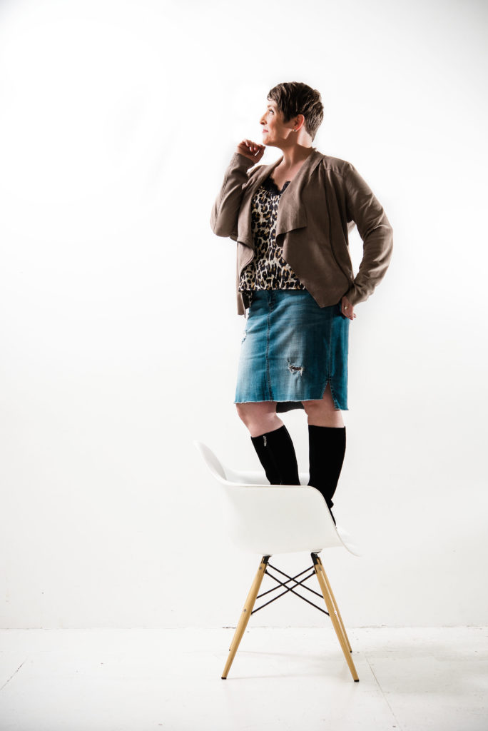 Woman posing while standing on a chair expressing confidence wearing a jean skirt with high boots, leopard blouse and a lite beige loosely fit jacket.