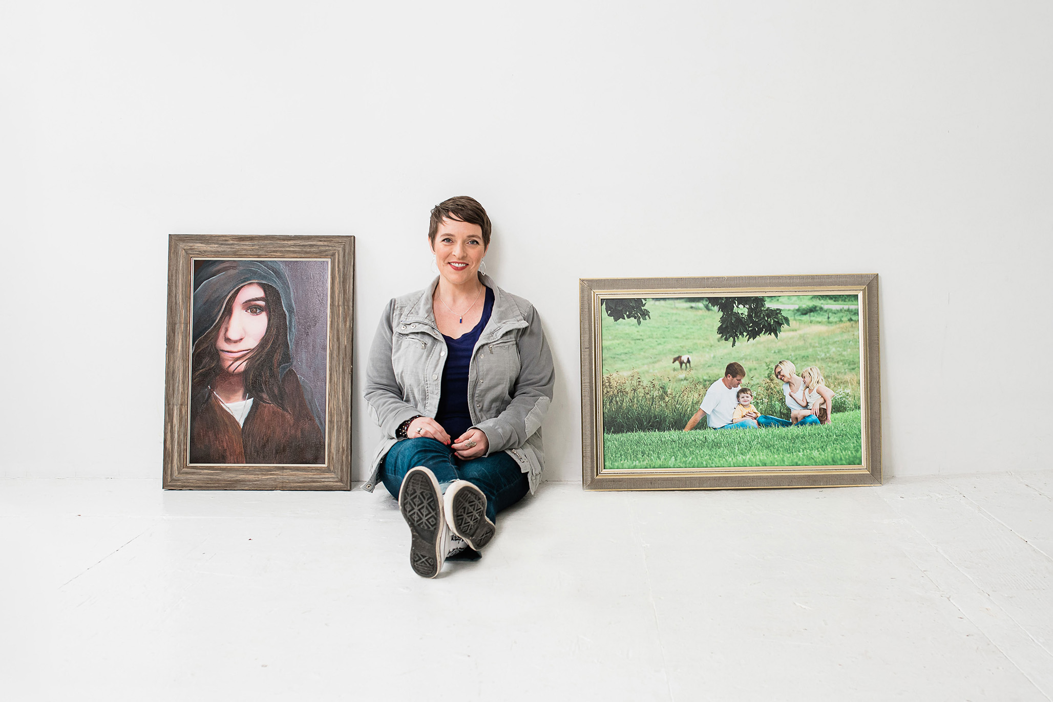 picture of woman sitting between two canvas portraits